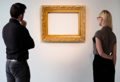 Man and woman looking at empty picture frame